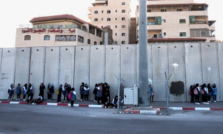 Palestinian schoolgirls wait for buses in the shadow of the Israeli wall, inside the Shua'fat refugee camp near Jerusalem.