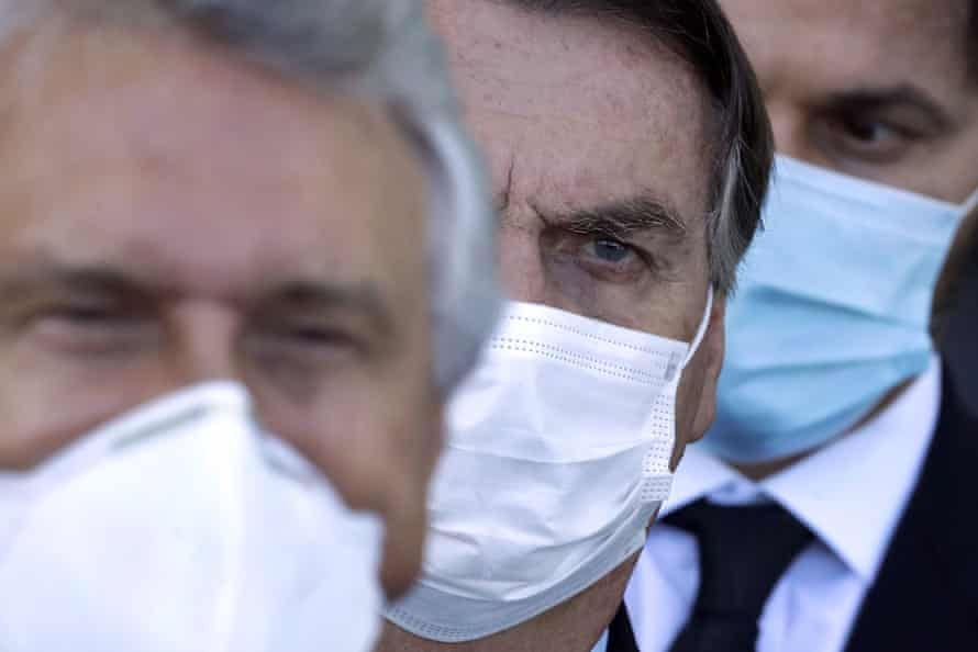 Bolsonaro, center, arrives for a press conference following a meeting about the federal government's response to coronavirus in Brasilia on Wednesday.
