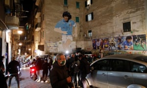 Mourners begin to congregate under a mural of the 'Golden Boy' in the Spanish Quarter of Naples