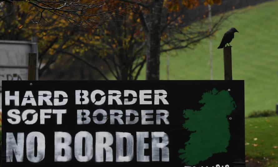 A bird sits near a sign calling for no border in Ireland