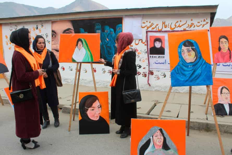 Attendees stand next to portraits of women who suffered violence at an exhibition in Faizabad, Badakhshan province in December 2019