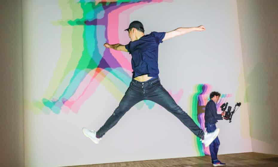 A visitor jumps and throws shapes with the installation Your Uncertain Shadow.