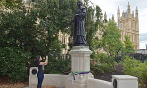 A woman takes a picture of the statue of the suffragette Emmeline Pankhurst