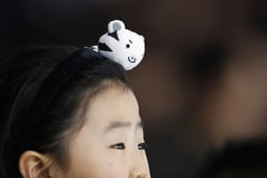 A girl wears one of the Olympic mascots as she watches the speedskating