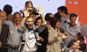 Opposition candidate, Buenos Aires mayor, Mauricio Macri, carries his daughter Antonia on the shoulders as his running mate Gabriela Michetti, right, looks on.