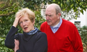 Older couple in a garden, she with her hand on her forehead in confusion, he leaning over her looking cross
