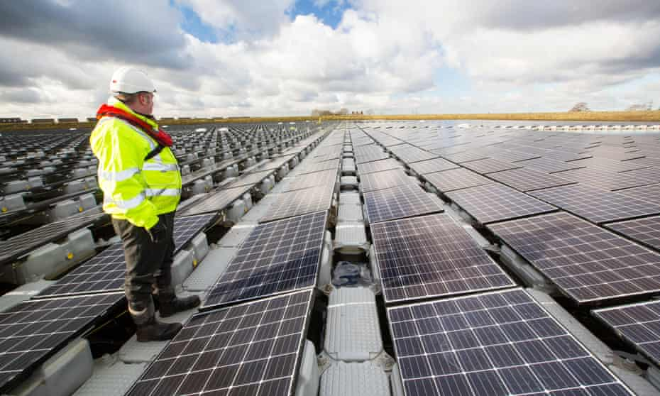 Staff inspect a new floating solar farm at Godley Reservoir in Hyde, Manchester