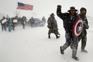 """Veterans join activists in a march to Backwater Bridge just outside the Oceti Sakowin camp during a snow fall as """"water protectors"""" continue to demonstrate against plans to pass the Dakota Access pipeline adjacent to the Standing Rock Indian Reservation, near Cannon Ball"""