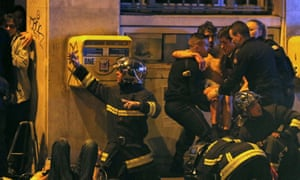 Members of the French fire brigade help an injured individual near the Bataclan concert hall