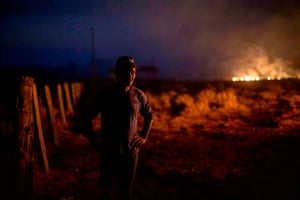 Brazilian Neri dos Santos, 48, looks at a fire at the farm where he works in Nova Santa Helena municipality, Mato Grosso state, in the Amazon basin, Brazil, on August 23, 2019.