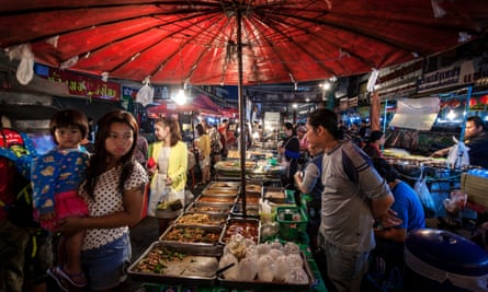 Customers walk around food stalls at Warorot evening market, in Chiang Mai, Thailand.