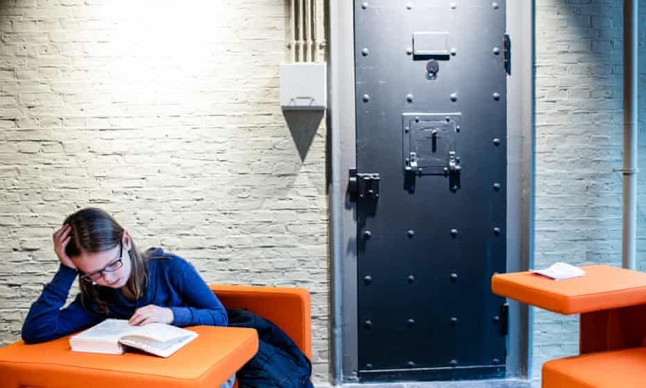 A girl sitting at a table reading a book in a cell at Blokhuispoort, a prison-turned-library.