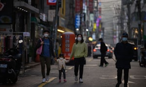 Pedestrians wearing face masks make their way along a street in Seoul on November 16, 2020. (Photo by Ed JONES / AFP)