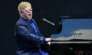 Elton John sits at a piano and sings