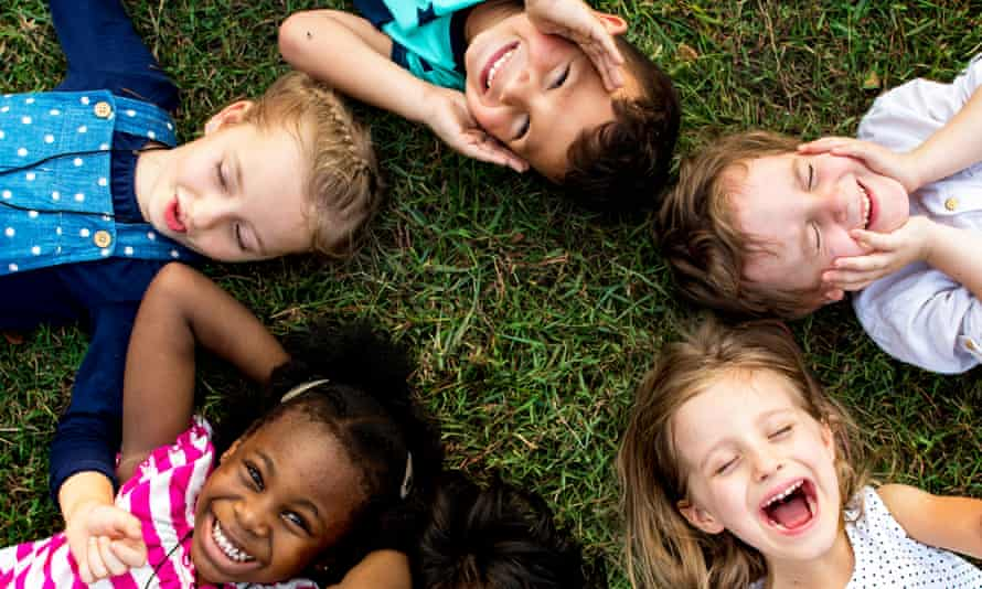 Group of kindergarten kids lying on the grass