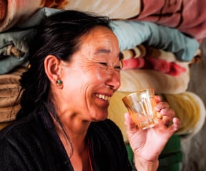 A woman drinking home-brewed raksi in Lo Manthang, Nepal.