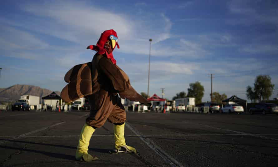 A man dressed in a turkey costume helps direct traffic at a free Thanksgiving food distribution event by the Culinary Academy Las Vegas for people affected by the coronavirus pandemic on Saturday.