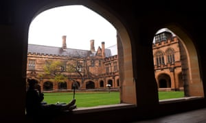 A student sits next to the quadrangle at the University of Sydney.