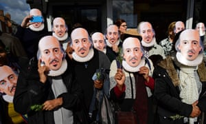 People wearing masks of the bard of Avon prepare for the parade