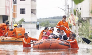 A family is rescued from a flooded residential area following heavy rains in Chennai