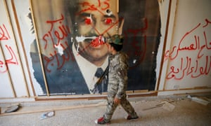 A fighter from the Iraqi Shia Badr Organisation looks at a poster depicting images of Saddam Hussein on the outskirts of Falluja. REUTERS/Thaier Al-Sudani