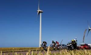 The lead group pass a wind turbine.