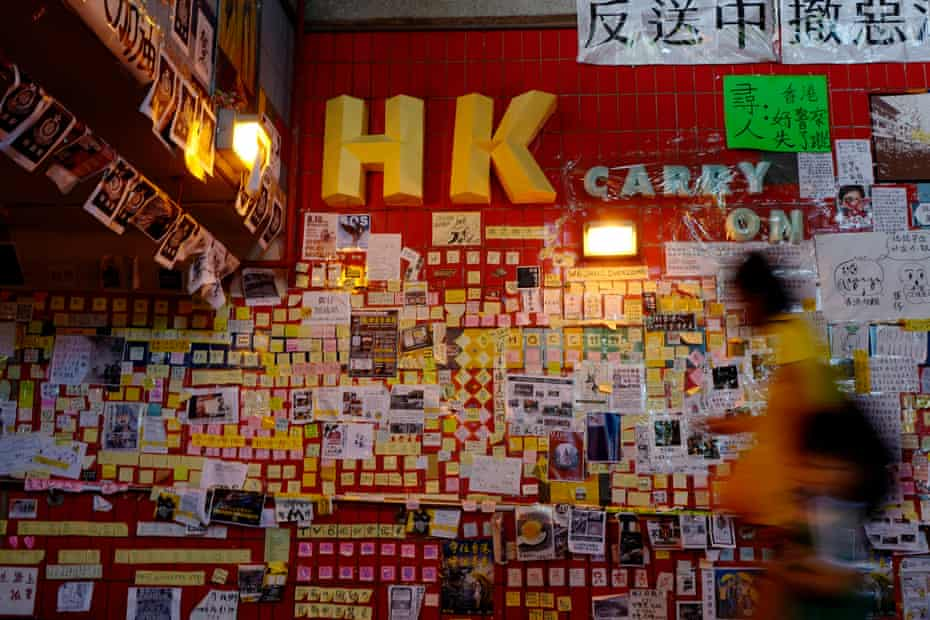 A resident walks next to a Lennon Wall exhibition, featuring messages supporting Hong Kong's pro-democracy protests.