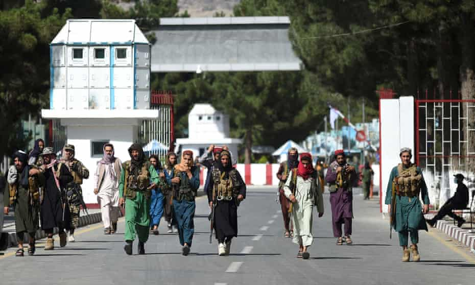 Taliban fighters walk in at the main entrance gate of Kabul airport on Saturday.
