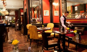 L'Escargot dining room with a waiter setting a table