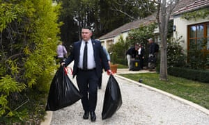 Australian federal police officers are seen leaving with evidence bags after a raid on a house in Canberra belonging to an intelligence officer Cameron Gill.