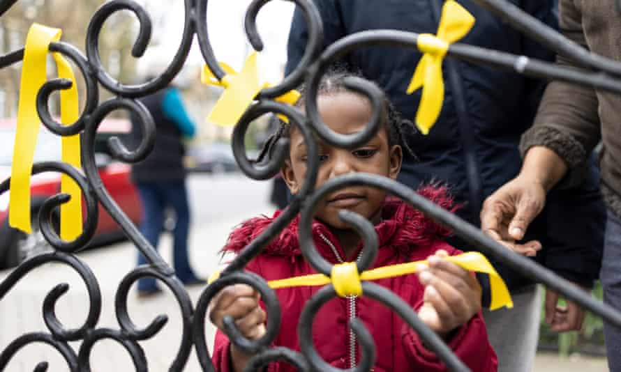 Angel Connolly ties a yellow ribbon to a gate after a small service at St Catherine's church in London