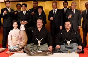 Accompanied by stable master Tagonoura (bottom right), Tagonoura's wife (bottom left) and supporters, sumo wrestler Kisenosato holds up a big sea bream to celebrate his promotion to the top rank of Yokozuna in January 2017