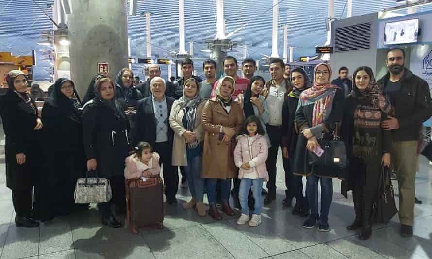 Mohammad Elmi, center back in red, said goodbye to friends and family at the airport in Tehran before leaving for California.