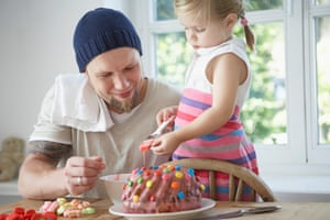 Father and daughter icing a cake.