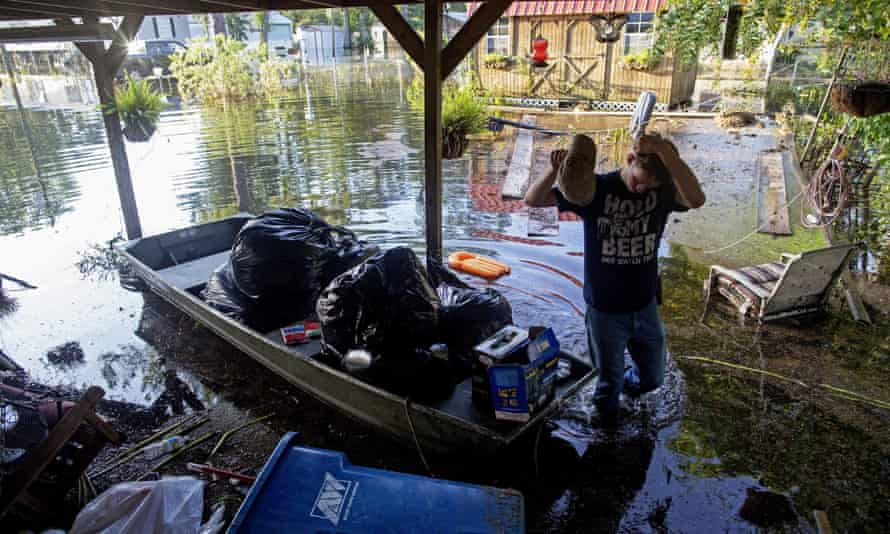 Daniel Stover, 17, wipes his head as he helps rescue people's belongings in Sorrento, Louisiana, on Saturday.