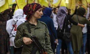 A member of the Kurdish internal security services known as Asayish stands guard during a demonstration by Syrian Kurds against the Turkish assault on north-eastern Syria in Qamishli on 28 October.