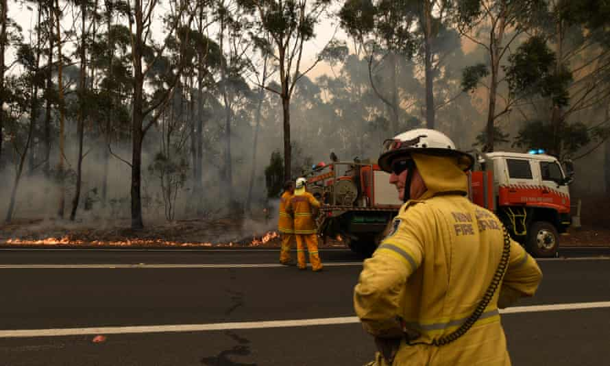 Firefighters extinguish a blaze by the side of a road