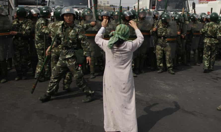 A Uighur woman protests before a group of Chinese paramilitary police in China's Xinjiang region in 2009.