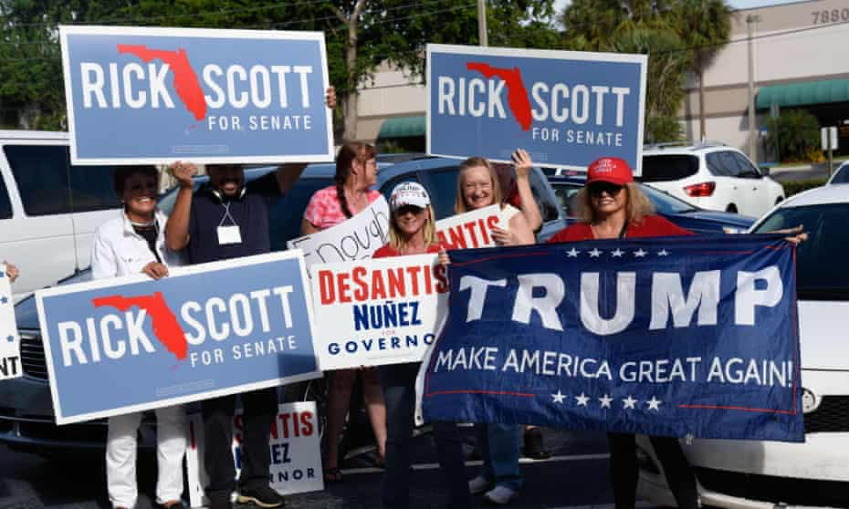Republican supporters hold signs in West Palm Beach, Florida, with tense recounts under way.