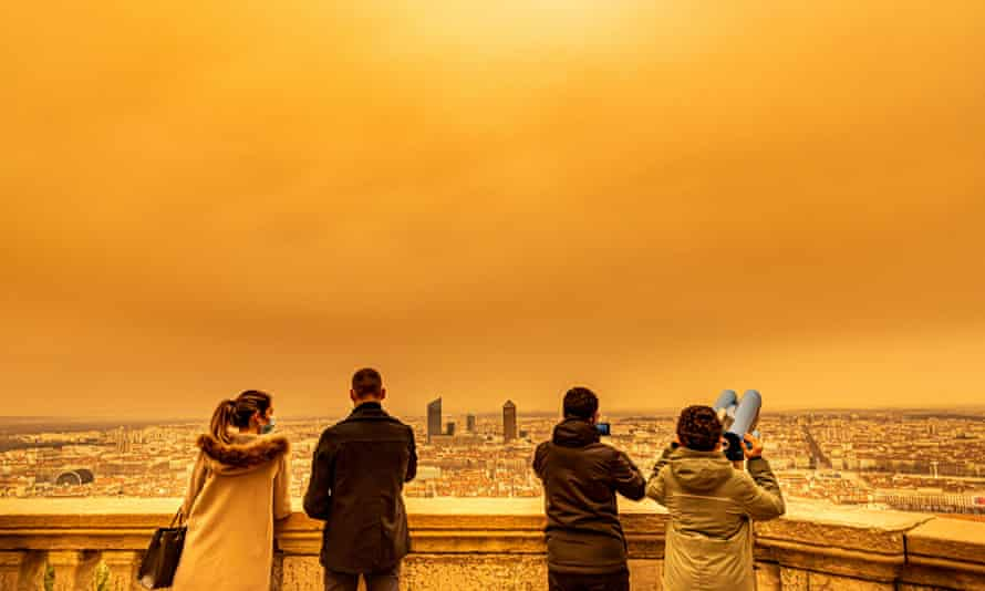 People looking at the panoramic view of Lyon from fourviere in the morning with a yellowish-orange sky over the city of Lyon.