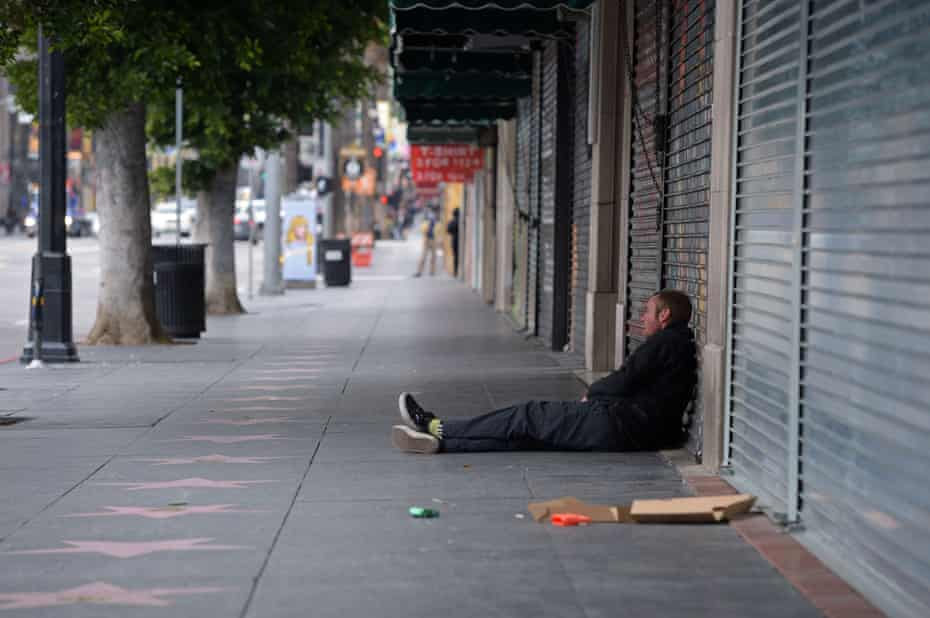 A man sits in front of a row of shuttered shops along Hollywood Boulevard in LA.