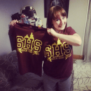 Charlotte holding a new Buffy t-shirt after the one she is wearing in the photo was ripped by a cheetah