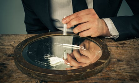 A businessman prepares to snort cocaine with a rolled-up banknote.
