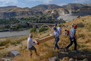 Workers carry a coffin from the old Hasankeyf cemetery to be moved to the new Hasankeyf cemetery on the banks of the Tigris