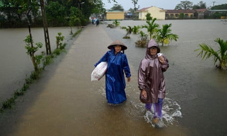 Women wade through flood waters in Quang Tri province on 16 October.