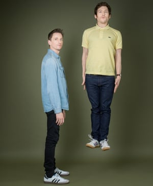 John Robins, standing side on, wearing a blue denim shirt and Elis James, jumping straight up, arms by his side, straight-faced, in a yellow polo shirt