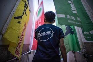 A member of Hong Kong's largest independent trade union walks through banners on display at its headquarters.