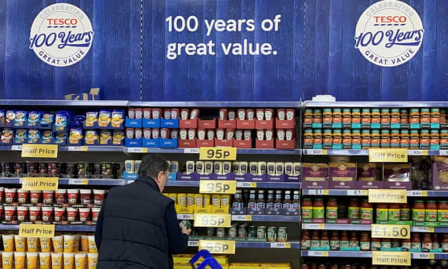 Man by tins of produce at a Tesco store.
