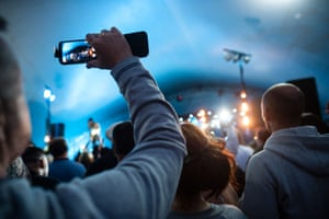 An audience member recording a band at a festival – millions of unauthorised videos end up on YouTube.
