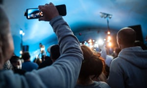 Audience member recording a band on their mobile phone